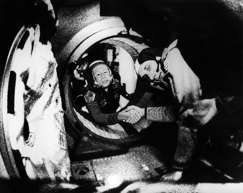 Alexey Leonov (left), commander of the Soyuz spacecraft's Soviet crew, and Thomas Stafford, commander of the Apollo's American crew, shake hands in space somewhere over West Germany after completing Apollo-Soyuz docking maneuvers, July 17, 1975. VCG