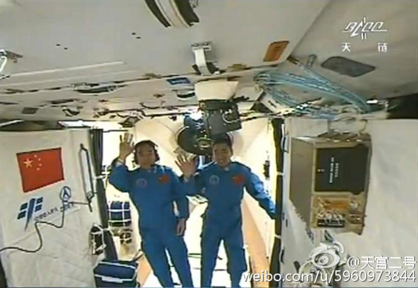 Chinese astronauts Jing Haipeng (left) and Chen Dong wave at a camera in the Tiangong 2 space station, October 2016. @tiangongerhao from Weibo