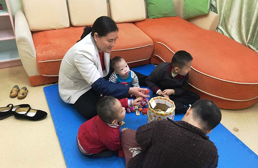 Li Songlan (left) plays with four children in her 'simulated family' apartment in Suzhou, Jiangsu province, Oct. 31, 2016. Fan Yiying/Sixth Tone