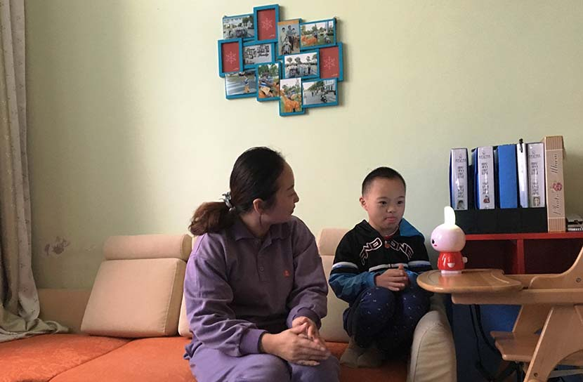 A member of staff from Suzhou Social Welfare Institute (left) sits with Shan Shan as he sings along with a musical rabbit toy in Lu Qinqin's 'simulated family' apartment in Suzhou, Jiangsu province, Oct. 31, 2016. Fan Yiying/Sixth Tone