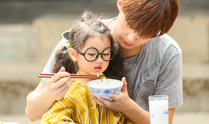 A still from 'Dad, Where Are We Going?' shows Dong Li feeding his 'daughter.' From the TV show's official Weibo account