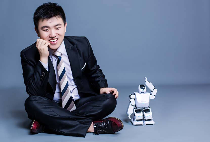 Leng Xiaokun poses for a photo with Aelos, his company's humanoid robot. Courtesy of Leju (Shenzhen) Robotics
