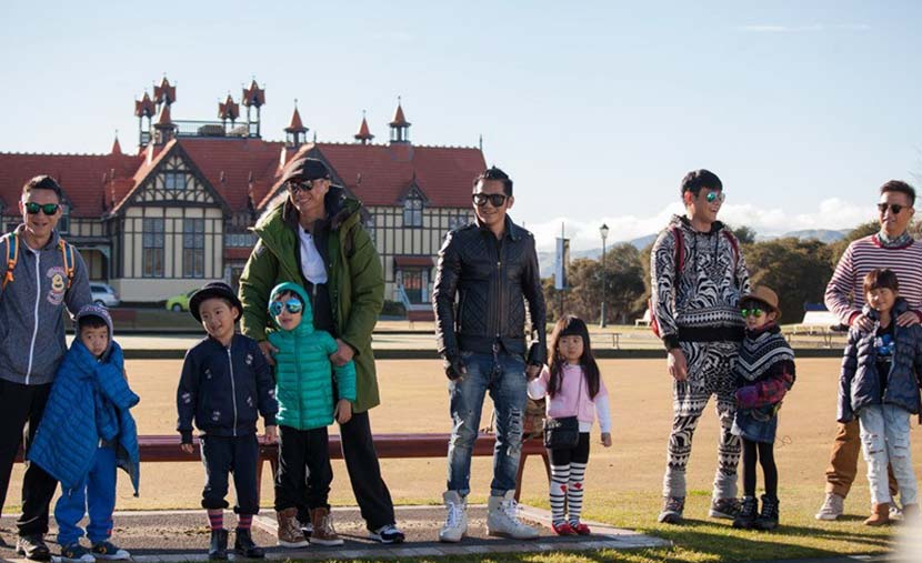 A still from the popular television show 'Dad, Where Are We Going?' shows fathers and their kids standing in front of a house in New Zealand. VCG
