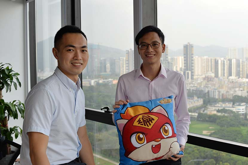 Sun Yue (left) and Li Tianchi pose with a pillow featuring one of the CodeMao cats in Shenzhen, Guangdong province, Oct. 23, 2016. Courtesy of CodeMao