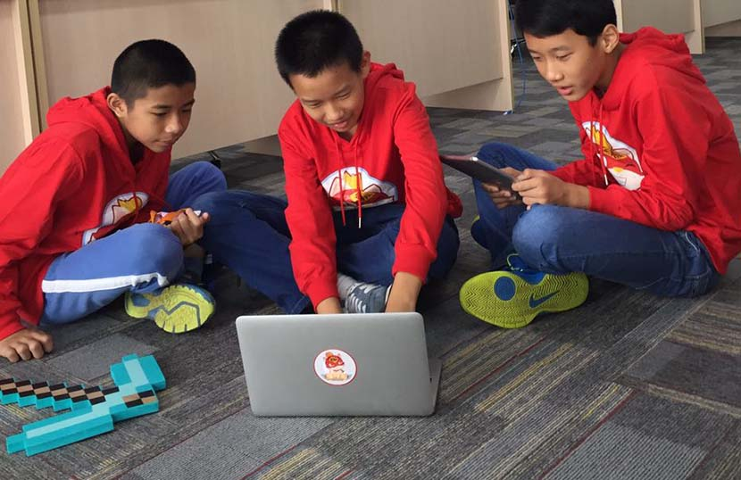 Wang Rong (middle), an 11-year-old in the Xinlian Primary School maker society, plays programming games with his friends at the CodeMao office in Shenzhen, Guangdong province. November 2016. Courtesy of Dai Qiming