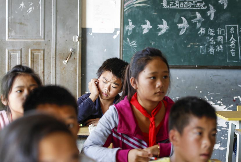 Li Xiaojin (back) rests his hand on his cheek during math class at Shuangyong Hope Project Primary School, Mohan City, Yunnan province, Nov. 18, 2016. Jia Yanan/Sixth Tone