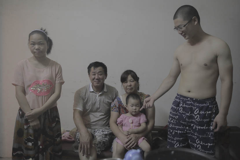 Li Shiping (second from left) and his family pose for a photo at home in Paizhouwan Township, Hubei province, Aug. 2, 2016. Zhou Pinglang/Sixth Tone