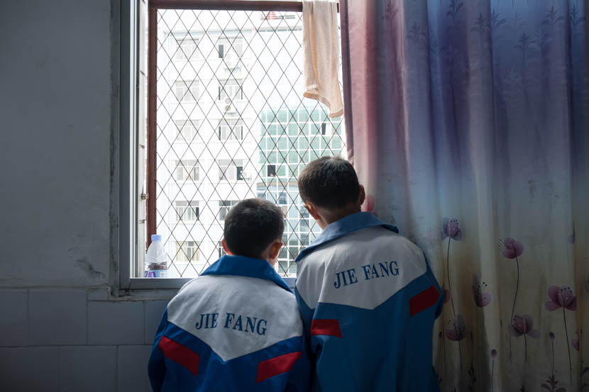 Wearing their school uniforms, Qiangcheng (left) and Yiqi look out of the window of their mother's room at Chaling County People's Hospital, Hunan province, Nov. 6, 2016. Zhou Na/Sixth Tone