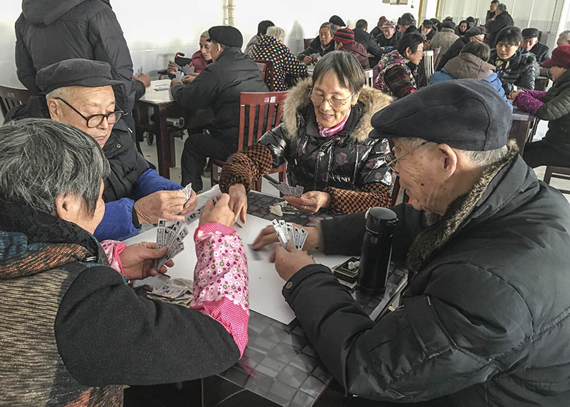 Jin Renzu (right), an 80-year-old former resident of Xinqiao Village, plays a card game with friends at a neighborhood community center on Chongming Island, Shanghai, Jan. 28, 2017. Ni Dandan/Sixth Tone