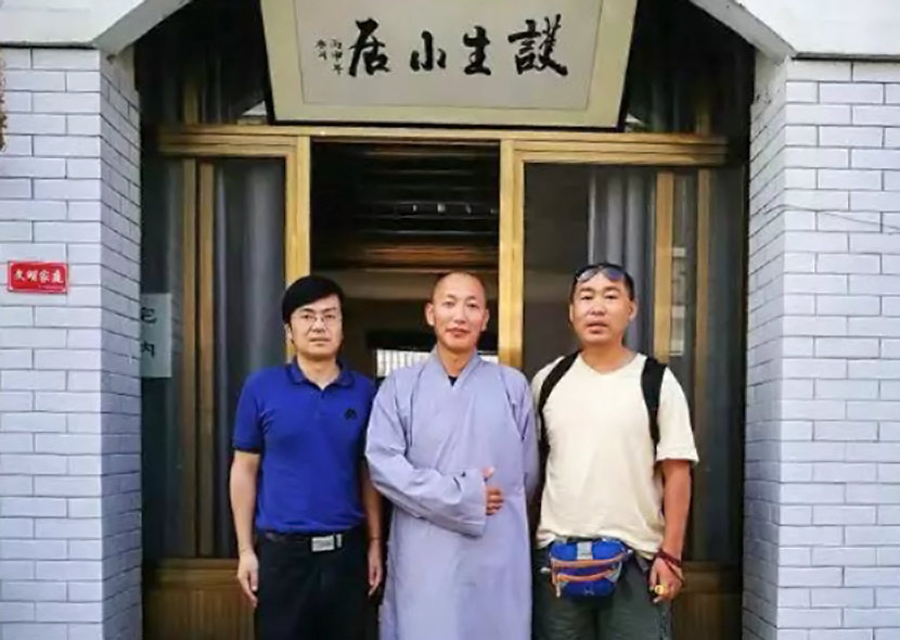 Dao Lu (middle) and donors pose for a photo at the entrance to Husheng Xiaoju in Nantong, Jiangsu province. From WeChat public account Umalotus
