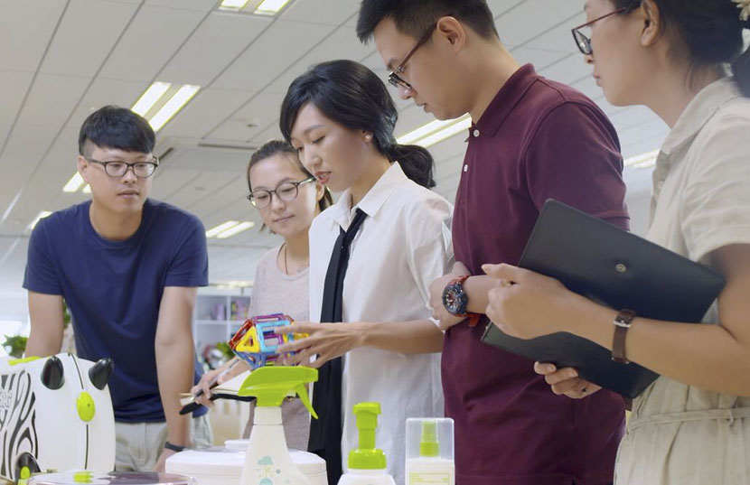Li Danyang (middle) examines baby products with her colleagues at Niangao Mama's office in Hangzhou, Zhejiang province, July 2016. Courtesy of Li Danyang