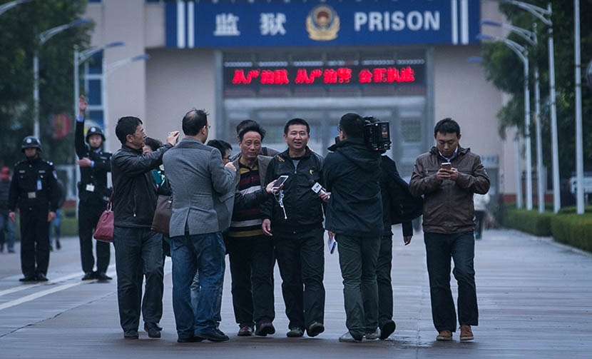 Chen Man (fourth from right) walks out of Meilan Prison where he is met by reporters waiting outside to interview him, Haikou, Hainan province, Feb. 1, 2016. He was found innocent after 23 years in jail. VCG