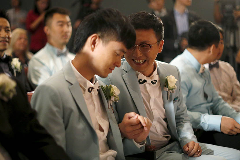 Duan Rongfeng (right) smiles at his newly-wed husband at a group wedding of seven Chinese same-sex couples in West Hollywood, California, U.S., June 9, 2015. Lucy Nicholson/VCG