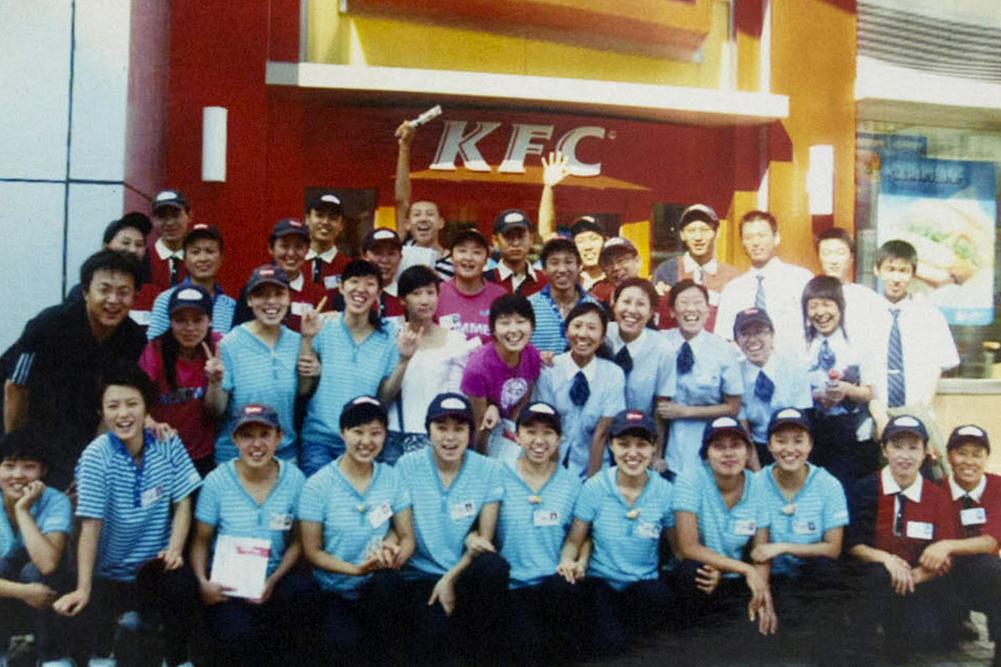 Ru Dongying (second row, fourth from left) and Yang Kun (back row, third from left) pose with colleagues in a photo taken in 2009. Following graduation Ru continued working part-time at KFC to supplement her low starting salary at a state-owned mining company. Provided by Ru Dongying