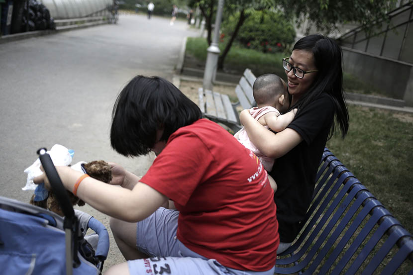Li Zikun (in black), a social worker with the Children's Hope Foundation, holds Sisi's baby girl as Sisi plays with a pet dog, Beijing, June 7, 2016. Han Meng/Sixth Tone