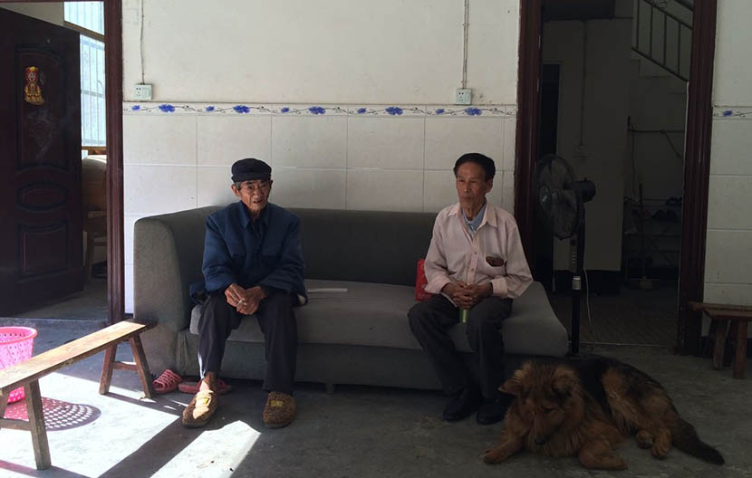 He Yanqing (left), who arrested Chen Jiaqian in 1975 while serving as a militiaman, sits with Chen during an interview at his home in Shawan Village, Leibo County, Sichuan province, July 2016. Zhou Jianping/Sixth Tone